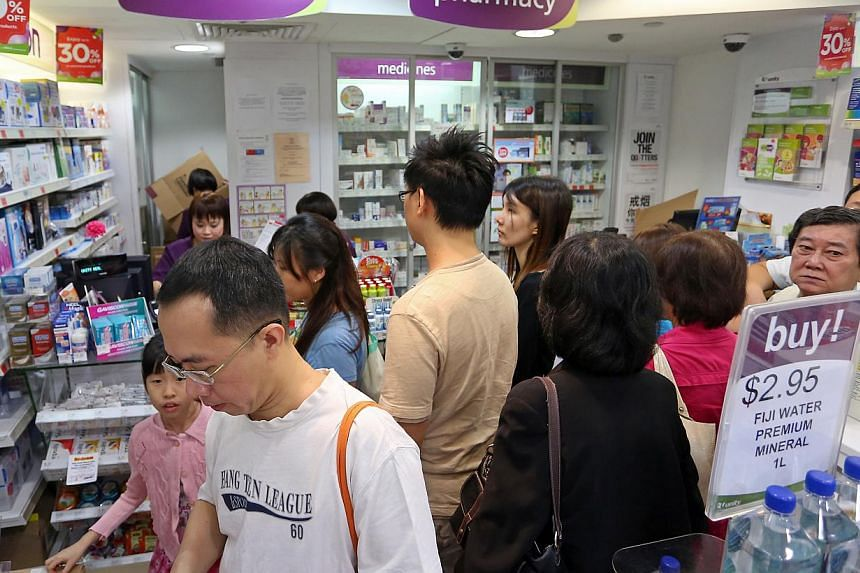Customers queue up at Unity Phamarcy at Plaza Singapura's basement for the new batch of N95 masks on June 22, 2013.As the haze disappears from Singapore skies, demand for the N95 masks has followed suit. -- ST FILE PHOTO: EDWARD TEO