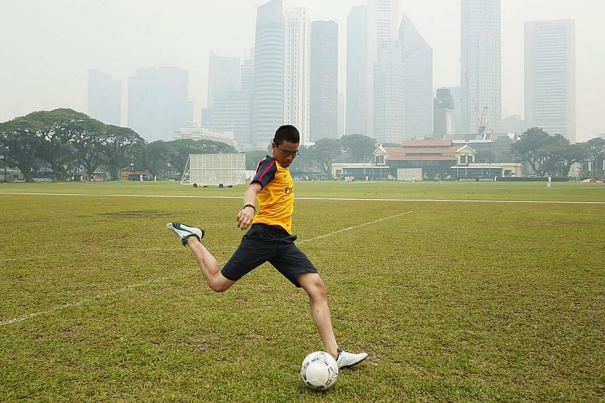 Mr Jared Lee, 18, playing football on a hazy day last month when the PSI read 95. Climate scientist Matthias Roth says the index should be modified to consider the PM2.5 particles to better reflect the haze's health impact.