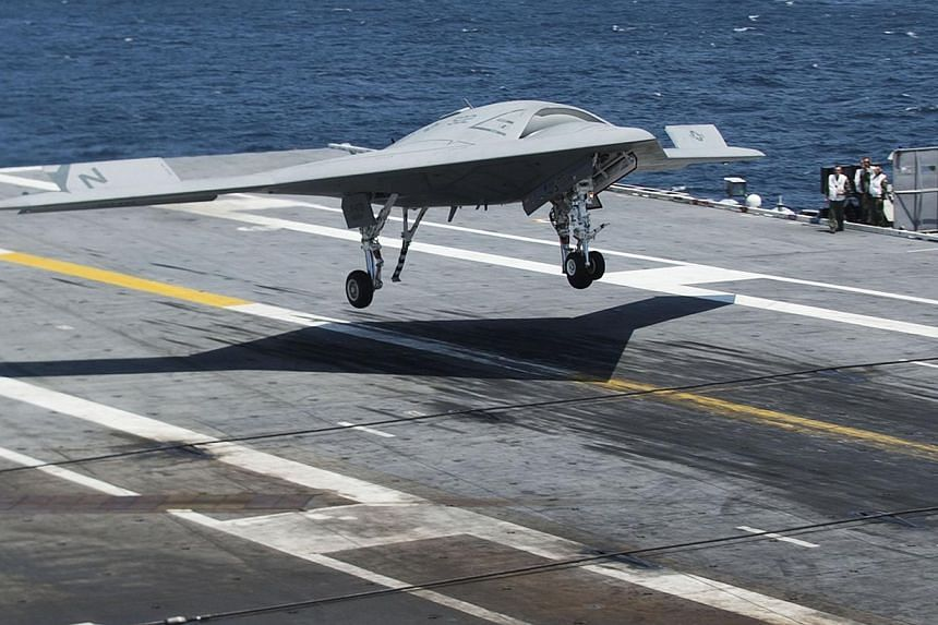 An X-47B Unmanned Combat Air System (UCAS) makes the very first carrier landing aboard the USS George H.W. A bat-winged drone touched down smoothly on the deck of a US aircraft carrier on Wednesday, marking a historic milestone for robotic flight. --