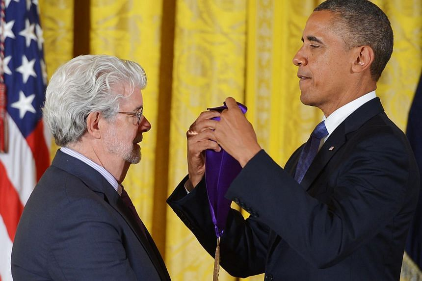 US President Barack Obama presents the 2012 National Medal of Arts to director George Lucas during a ceremony in the East Room of the White House on July 10, 2013 in Washington, DC. -- PHOTO: AFP