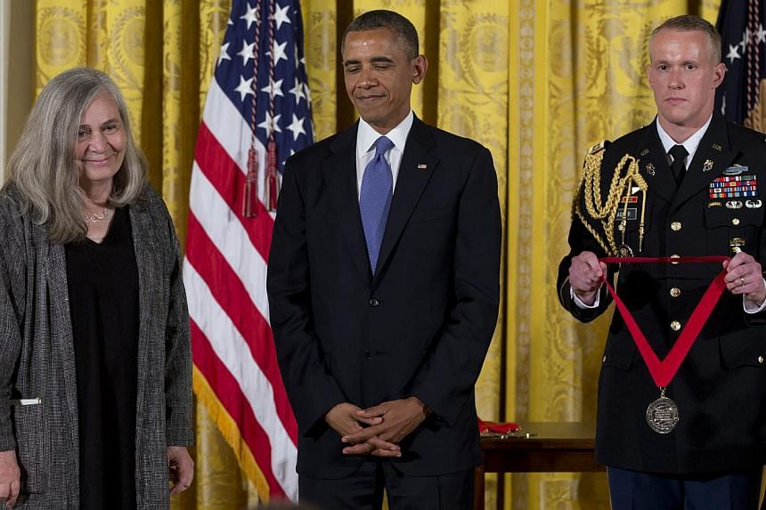 President Barack Obama stands with Marilynne Robinson as he awards her the 2012 National Humanities Medal for her grace and intelligence in writing, during a ceremony in the East Room of White House, Wednesday, July 10, 2013, in Washington. -- PHOTO: