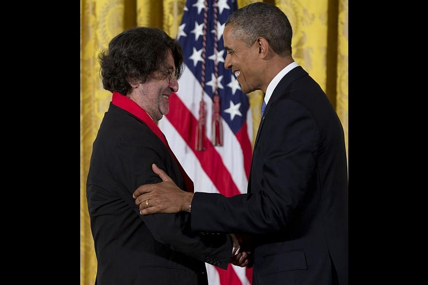 President Barack Obama awards Camilo José Vergara the 2012 National Humanities Medal for his stark visual representation of American cities, during a ceremony in the East Room of White House, Wednesday, July 10, 2013, in Washington. -- PHOTO: AP