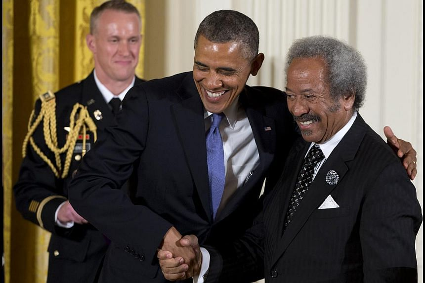 President Barack Obama welcomes Allen Toussaint to the stage to award him the 2012 National Medal of Arts for his contributions as a composer, producer, and performer, Wednesday, July 10, 2013, during a ceremony in the East Room of White House in Was