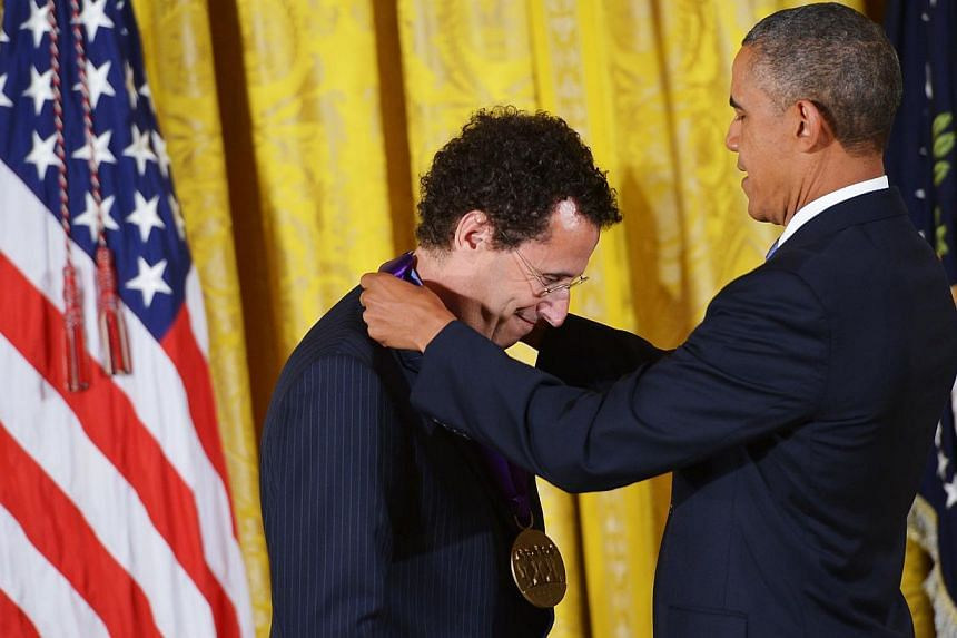 US President Barack Obama presents the 2012 National Medal of Arts to playwright and screenwriter Tony Kushner during a ceremony in the East Room of the White House on July 10, 2013 in Washington, DC. -- PHOTO: AFP