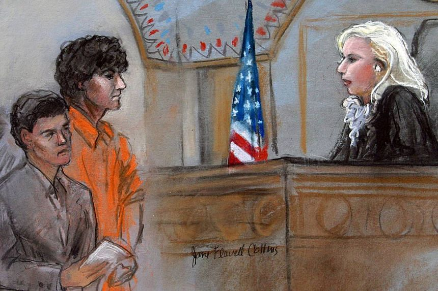 This courtroom sketch depicts Boston Marathon bombing suspect Dzhokhar Tsarnaev standing with his lawyer Judy Clarke (left) before Magistrate Judge Marianne Bowler (right) during his arraignment in federal court in Boston on July 10, 2013. Wearing an
