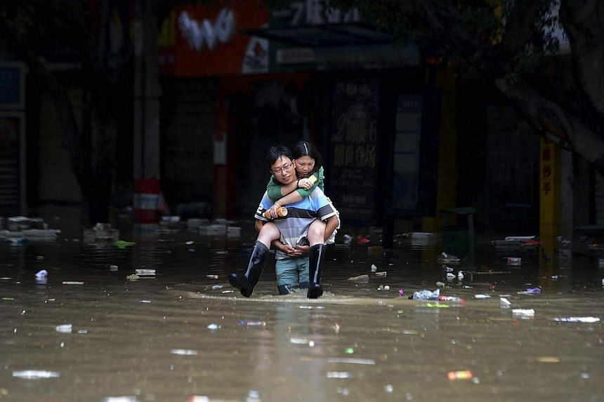 A man carries a woman on his back as he walks through a flooded street in Jintang county of Chengdu, Sichuan province on July 10, 2013. Heavy rain across China has left at least 28 people dead and 66 missing, officials reported on Thursday, July 11,