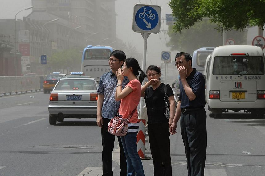 People try to protect themselves against air pollution and dust along a street in Beijing on May 19, 2013. The United States (US) and China, the world's top emitters of greenhouse gases, agreed to five initiatives on Wednesday to cut carbon output fr
