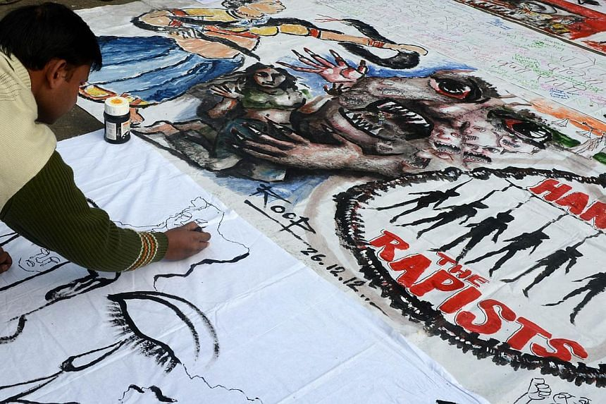 An Indian bystander writes on a banner as it lies on a road in New Delhi on Dec 30, 2012. A New Delhi court was set to deliver the first verdict on Thursday, July 11, 2013, on one of five suspects on trial over the fatal gang-rape of a student on a m