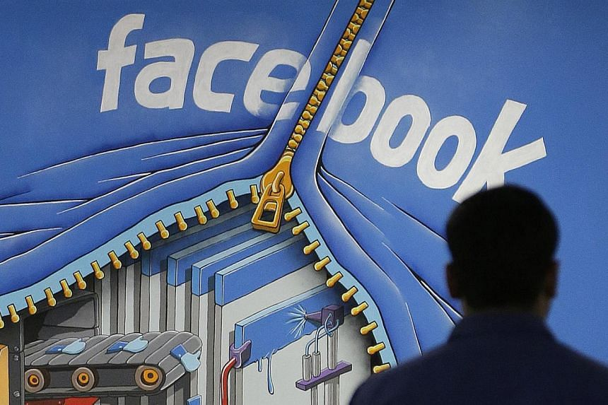 A Facebook employee walks past a sign at Facebook headquarters in Menlo Park, California on March 15, 2013. A government minister in Venezuela, which has offered fugitive US intelligence leaker Edward Snowden asylum, is urging her countrymen to cance