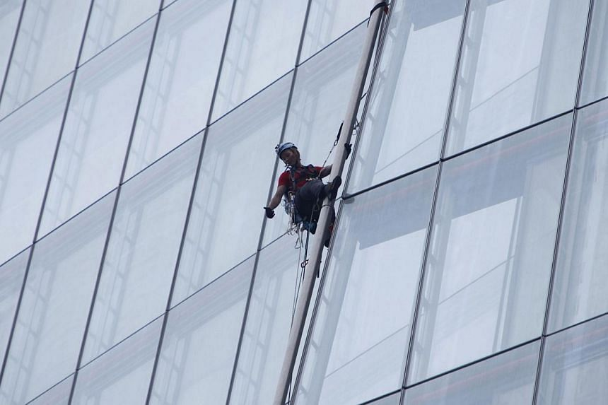 A Greenpeace demonstrator gestures during her ascent of the Shard skyscraper in London on Thursday, July 11, 2013. Six female Greenpeace activists attempted on Thursday to scale the Shard skyscraper in London, western Europe's tallest building, in a