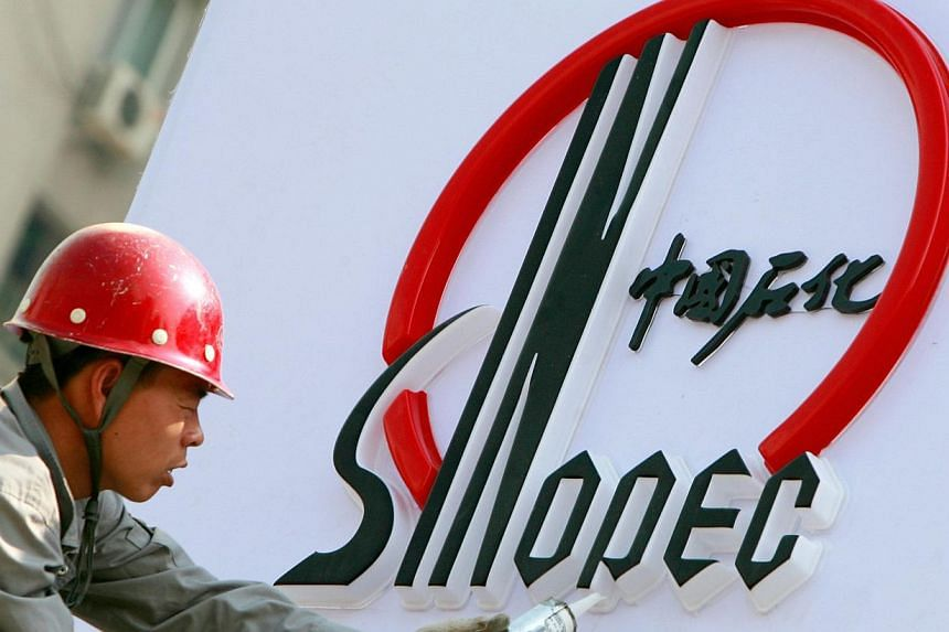A Chinese worker installs a Sinopec logo at a new Sinopec station in Beijing. Chinese oil giant Sinopec opened its lubricant plant in Tuas on Thursday, July 11, 2013, its first outside of China.  -- FILE PHOTO: AFP