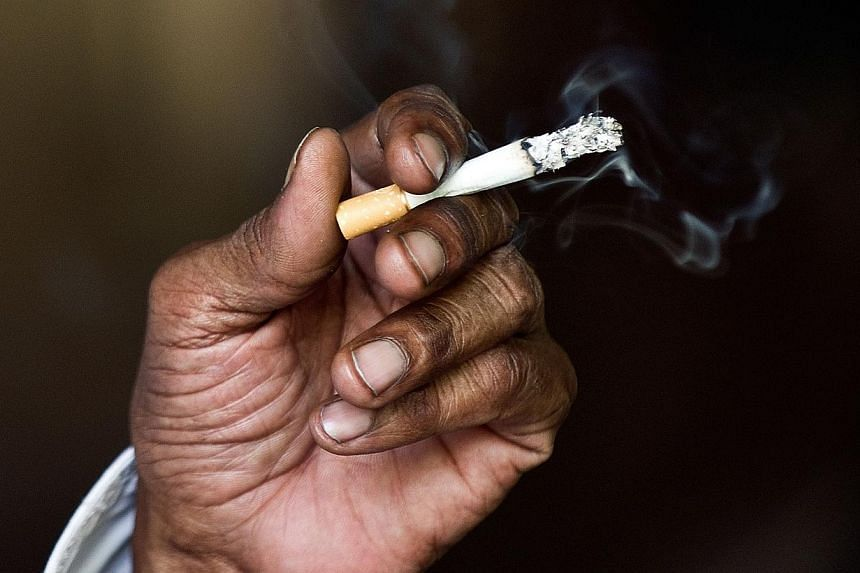 An Indian man smokes a cigarette in New Delhi in this May 31, 2013, file photo. Banning smoking in the workplace and levying a tobacco tax could prevent more than nine million deaths from cardiovascular disease in India over the next decade, accordin