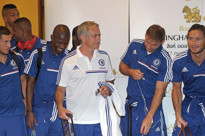 Chelsea football Manager Jose Mourinho (centre) talks with players before giving a traditional greeting after arriving at Suvarnabhumi International Airport in Bangkok on Friday, July 12, 2013. Chelsea football team will play an exhibition match agai
