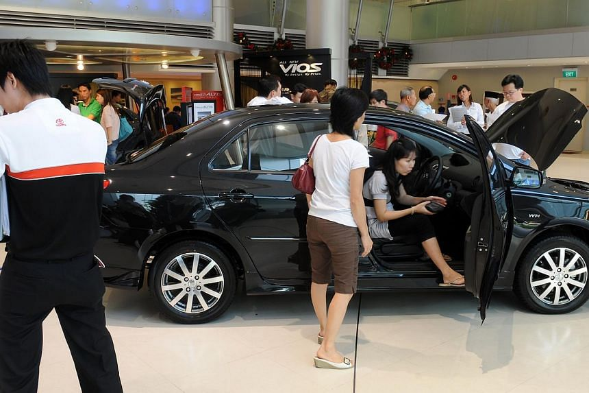 Potential buyers flooding a Totoya car showroom. More car buyers can bid for certificates of entitlement (COEs) from next month to January 2014, as the Government bumps up the quota for all categories of cars. -- ST FILE PHOTO: LAU FOOK KONG