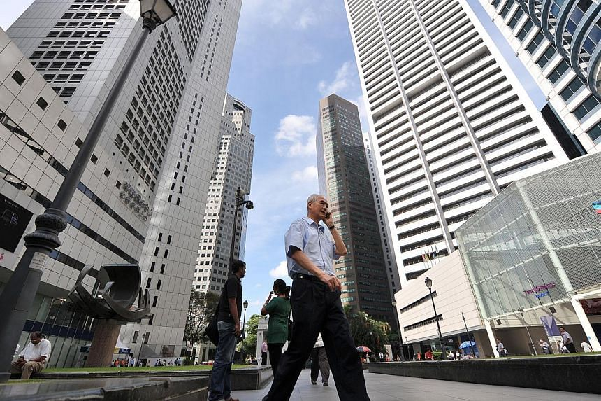 People walking along Raffles Place. A rebound in factory output and strong expansion in services propelled Singapore's economy to significantly faster growth in the second quarter, beating economists' expectations. -- ST FILE PHOTO: ALPHONSUS CHERN