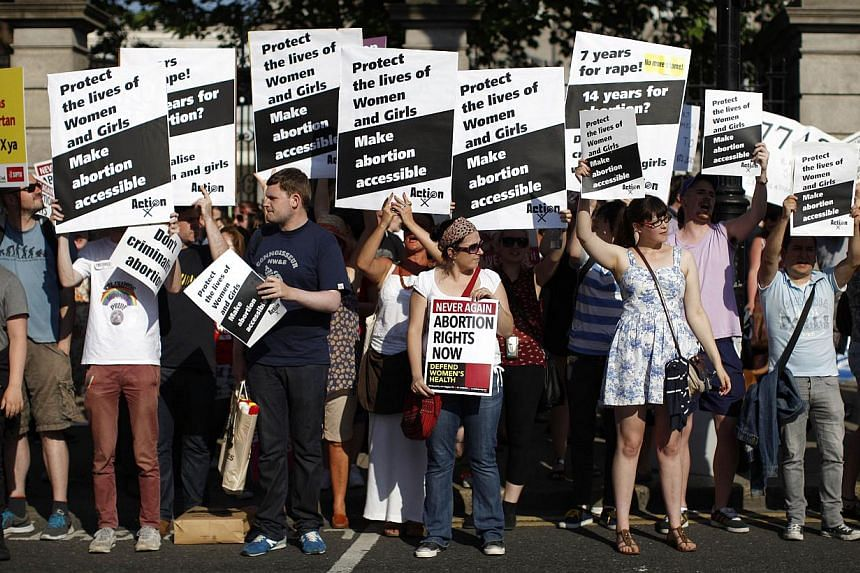 Pro-Choice supporters hold placards in front of the gates of the Irish Parliament building in Dublin on July 10, 2013 during a demonstration ahead of a vote to introduce abortion in limited cases where the mother's life is at risk. Ireland's parliame