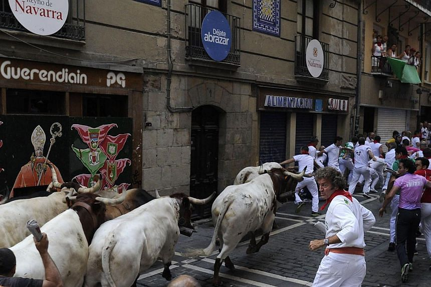 Participants run in front of Torrestrella's bulls during the bull run of the San Fermin Festival in Pamplona, northern Spain, on July 11, 2013. Two men fell and were injured on Thursday, including an American who broke his ankle, on the fifth day of