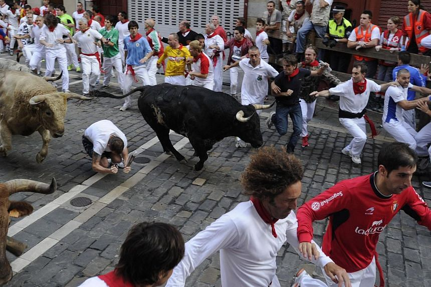 Participants run in front of Torrestrella's bulls during the fifth bull run of the San Fermin Festival in Pamplona, northern Spain, on July 11, 2013. Two men fell and were injured on Thursday, including an American who broke his ankle, on the fifth d
