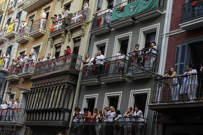 People on balconies watch participants running in front of Torrestrella's bulls during the fifth bull run of the San Fermin Festival in Pamplona, northern Spain, on July 11, 2013. Two men fell and were injured on Thursday, including an American who b