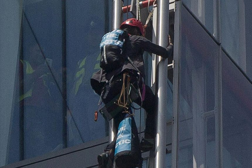 A Greenpeace demonstrator climbs the Shard building, in central London on July 11, 2013. Greenpeace said on its website that the six women attempting to climb the Shard, the tallest building in Western Europe, were protesting against drilling for oil