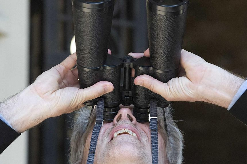 A man uses binoculars to look at Greenpeace demonstrators climbing the Shard building, in central London on July 11, 2013. Greenpeace said on its website that the six women attempting to climb the Shard, the tallest building in Western Europe, were p