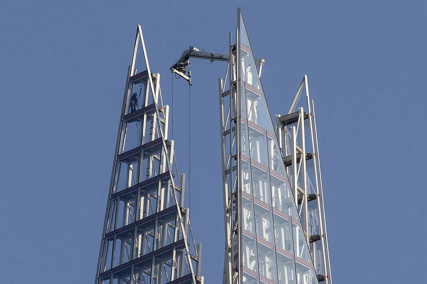 A Greenpeace protester climbs to the top of The Shard, the tallest building in western Europe, during a protest against the oil company Shell's drilling in the Arctic, on Thursday, July 11, 2013. -- PHOTO: AP