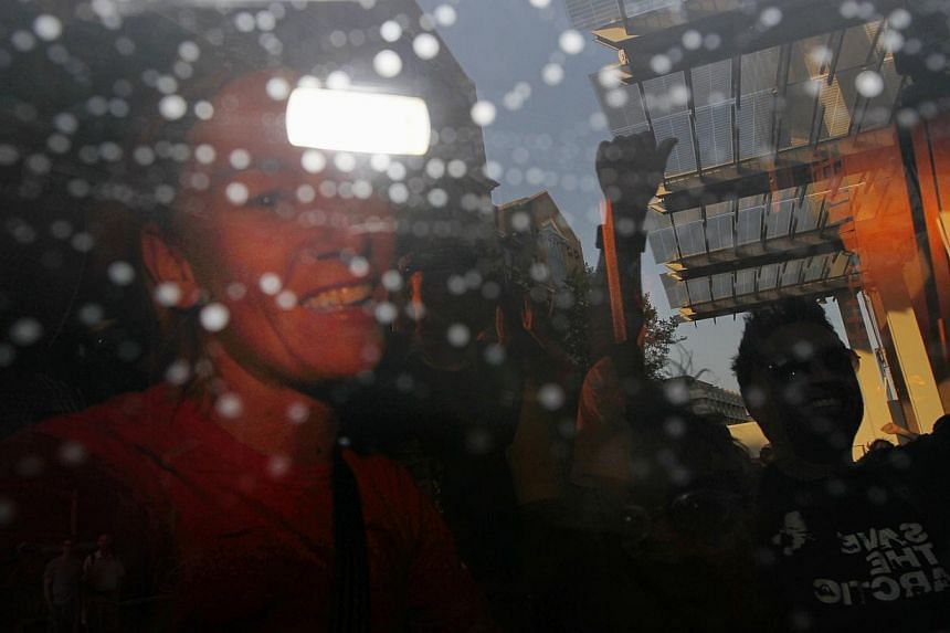 One of the unidentified Greenpeace protesters (left), reacts as she is being taken away in a police van after climbing up the Shard, the tallest building in western Europe, during a protest against the oil company Shell drilling in the Arctic, on Thu