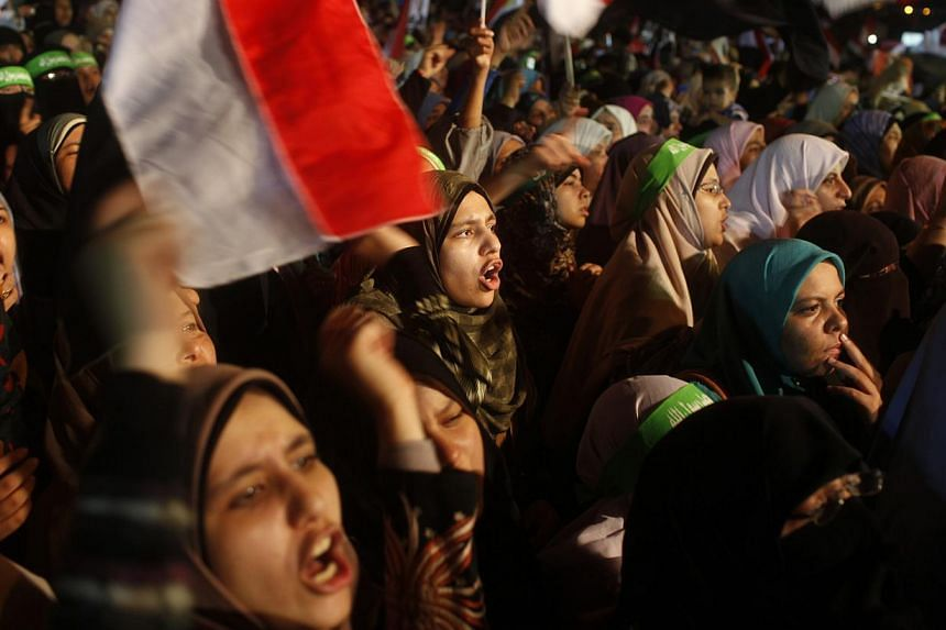 Supporters of Egypt's deposed President Mohamed Mursi shout slogans as they continue their sit-in outside the Rabaa Adawiya mosque, east of Cairo, on July 11, 2013. Supporters of ousted Mr Mursi called for protests on Friday, and Egyptians prayed the