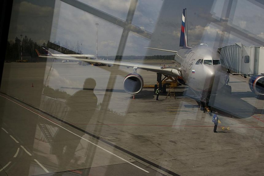 Through a window, the Aeroflot flight to Havana plane is seen parked for boarding next to a gate of Sheremetyevo airport outside Moscow, Russia, on July 9, 2013. Former US intelligence contractor Edward Snowden will meet human rights groups on Friday