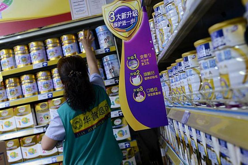 A saleswoman checks items for sale next to a shelf of milk powder at a supermarket in Beijing on July 4, 2013. Abbott Laboratories is cutting prices of its instant products in China by up to 12 per cent, the company said, joining other foreign firms
