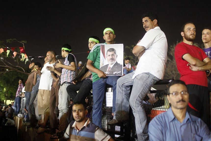A supporter of Egypt's deposed President Mohamed Mursi holds a poster of him (centre) while waiting with others as prayers are performed, during their sit-in outside the Rabaa Adawiya mosque, east of Cairo on July 11, 2013. Germany's Foreign Ministry