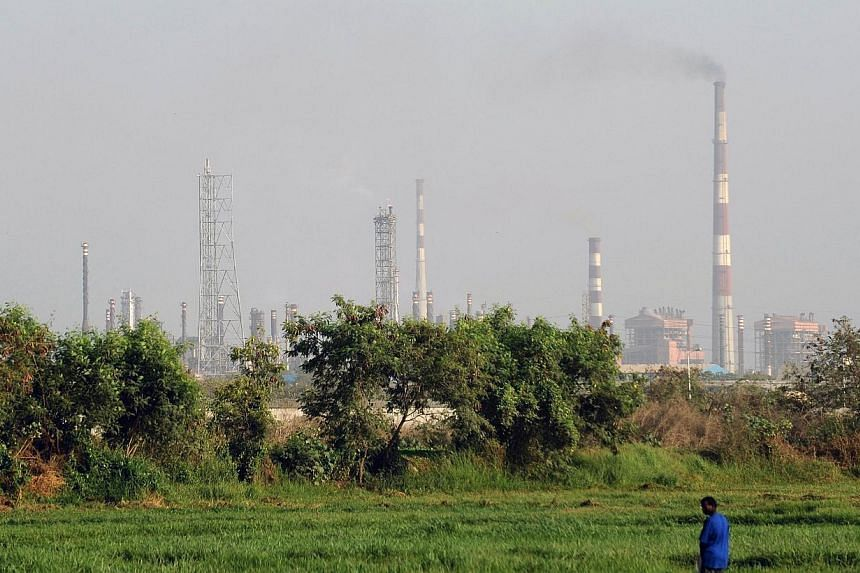 An Indian man stands in a field as factory chimneys from an industrial area loom in the background in Mumbai on April 22, 2013. India's industrial output slid by a surprise 1.6 per cent in May from a year earlier, official data showed on Friday,
