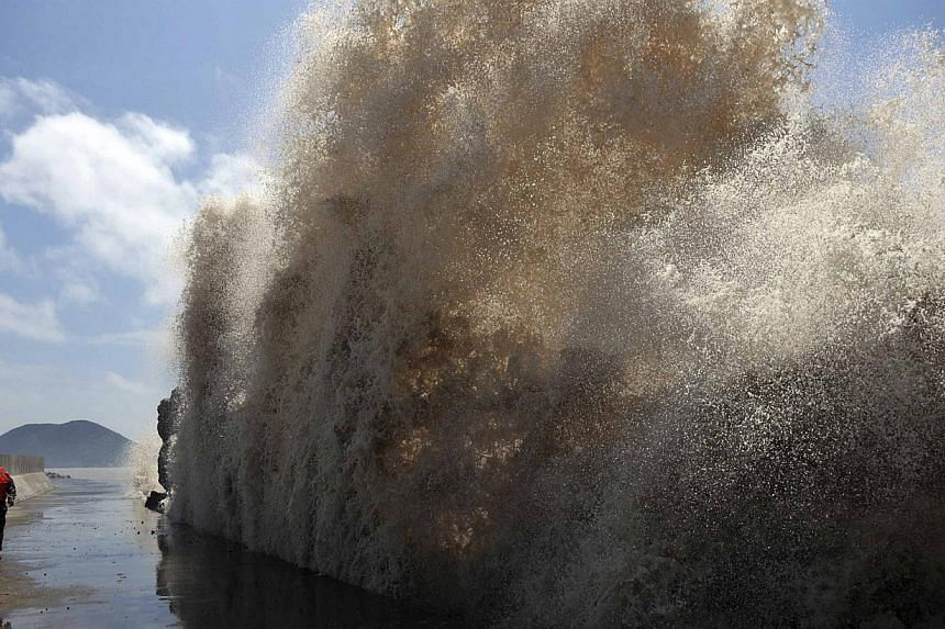 Frontier soldiers look up at the swell, as they carry out a check of a seawall, as Typhoon Soulik approaches in Wenling, Zhejiang province July 12, 2013. China braced on Friday for the impact of Typhoon Soulik as the toll of dead and missing from tor