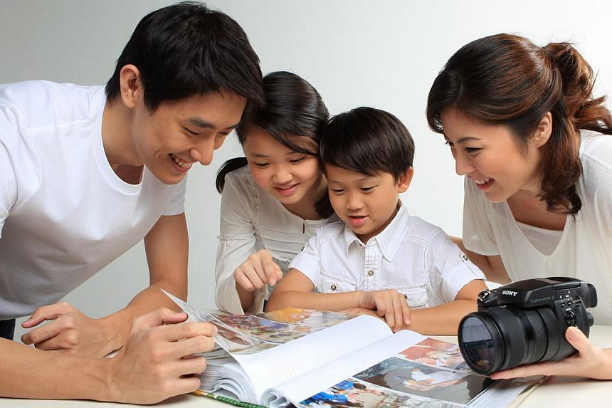 Posed photo of a family looking at a photo album. Family planning, higher education and quality time with loved ones are priorities for people around the world, according to a new global Nielsen survey focusing on lifestyle values released on Friday.