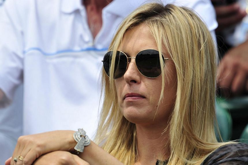 Russia's Maria Sharapova sits in the crowd watching the action on court number 3 on day four of the 2013 Wimbledon Championships tennis tournament at the All England Club in Wimbledon, south-west London, on June 27, 2013, one day after being beaten i
