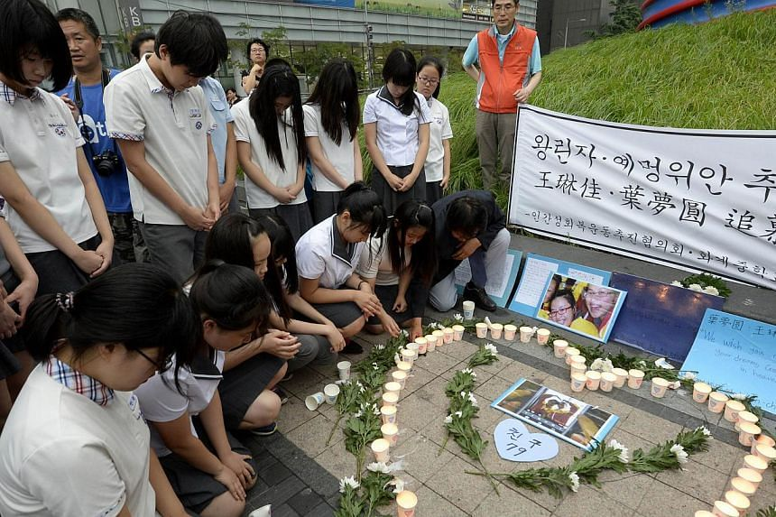 South Korean students pay a silent tribute in front of candles and pictures of Ye Mengyuan and Wang Linjia, both victims of the Asiana Airlines flight 214 crash, in central Seoul on July 11, 2013. One of the two teenage Chinese girls who died in the
