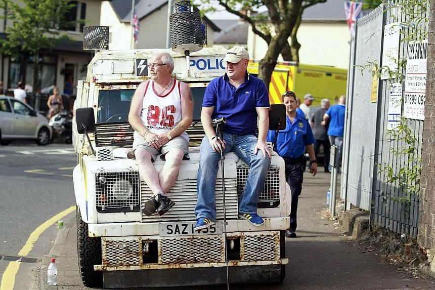 Loyalists sit on an armoured police Land Rover as an Orange Order parade passes through the nationalist ardoyne area of the Crumlin Road in Belfast on July 12, 2013. -- PHOTO: REUTERS