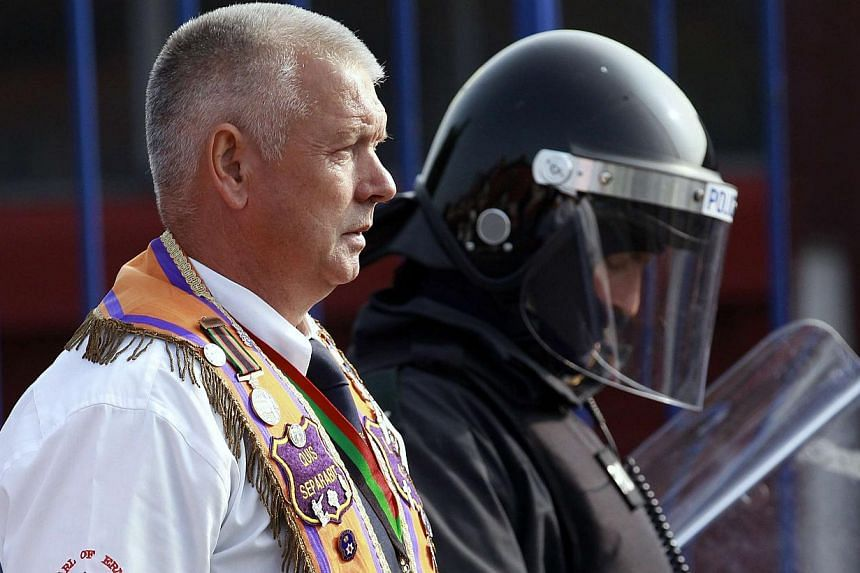A member of the Orange Order is flanked by a riot police officer during a march past the nationalist ardoyne area of the Crumlin Road in Belfast on July 12, 2013. -- PHOTO: REUTERS