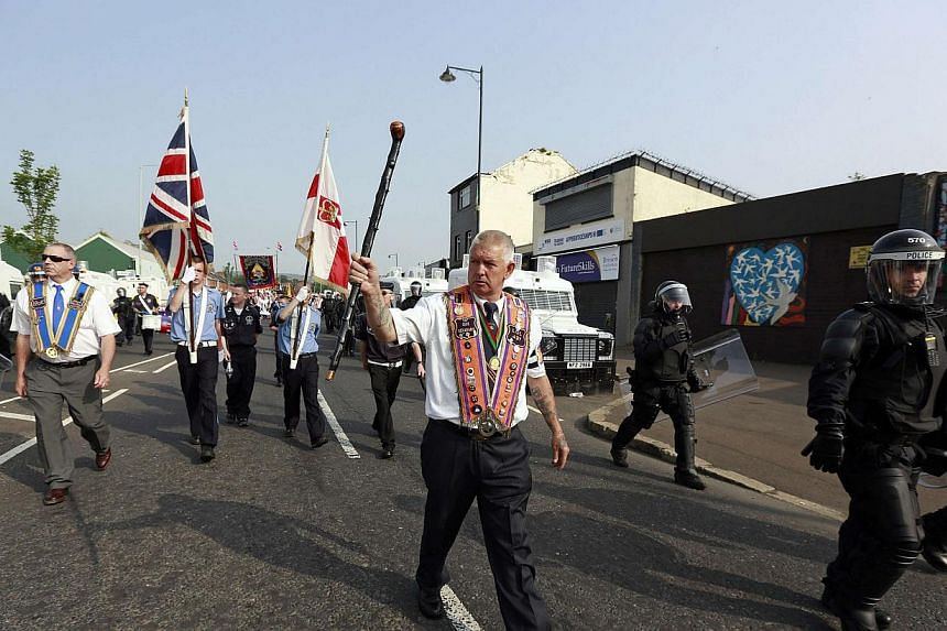 Members of the Orange Order are flanked by riot police as they march past the nationalist ardoyne area of the Crumlin Road in Belfast on July 12, 2013. -- PHOTO: REUTERS