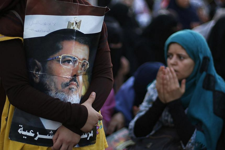 A supporter of the deposed Egyptian President Mohamed Mursi holds his picture during a protest in Cairo on July 12, 2013.The United States (US) on Friday called on Egypt's military to free deposed president Mohamed Mursi, as tens of thousands o