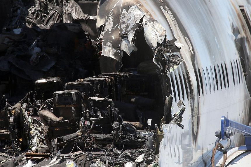 Burned seats are visible in the wrecked fuselage of Asiana Airlines flght 214 as it sits in a storage area at San Francisco International Airport on July 12, 2013 in San Francisco, California. -- PHOTO: AFP