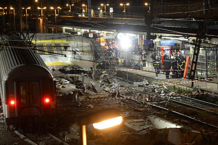 Rescuers work at night on the site of a train accident on July 12, 2013 at the railway station of Bretigny-sur-Orge, near Paris. At least six people were killed and dozens injured on Friday after a speeding train derailed at a station in the southern
