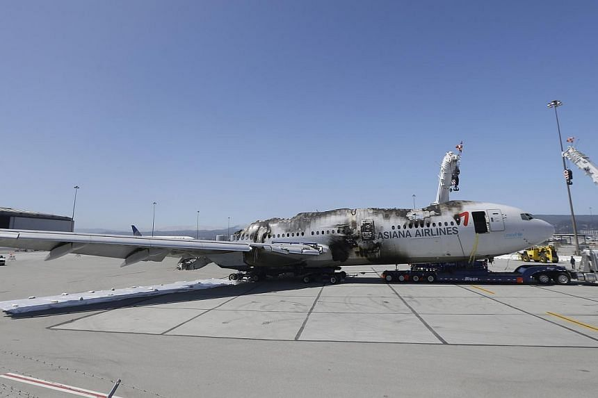 The wreckage of Asiana Flight 214, which crashed on Saturday, July 6, 2013, is seen at San Francisco International Airport in San Francisco on Friday, July 12, 2013. US officials apologised on Friday for mistakenly confirming false and offensive name