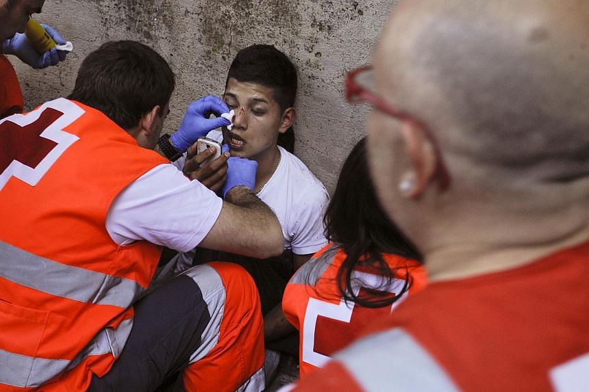 A wounded man is attended to by medical services outside of the bull ring as runners trip and fall ahead of the bulls blocking the entrance to the bullring during the running of the bulls of the San Fermin festival, in Pamplona northern Spain on Satu