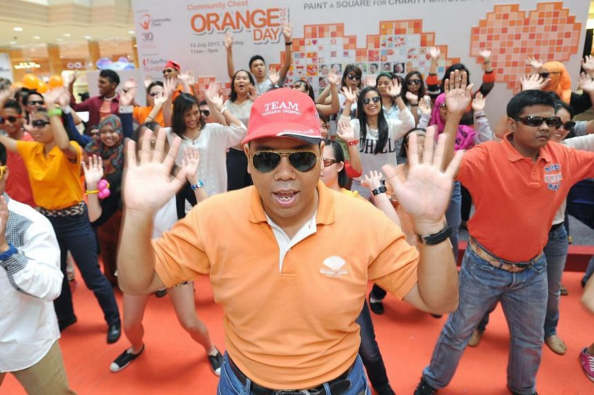 Mr Mohd Farhan Mohamed Noor, 25, (centre) one of the beneficiaries of SIA-MINDS Employment Development Centre participates in a flash mob performance together with volunteers from Temasek Polytechnic at the first Community Chest Orange Day at Wisma A