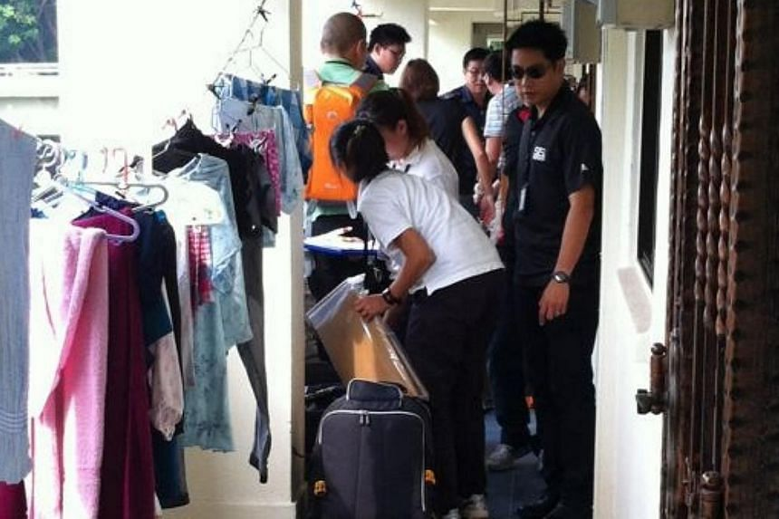 Plain-clothes police arrived at the Kim Keat flat of Kovan murder suspect Iskandar Rahmat on Saturday. -- ST PHOTO: PEARL LEE