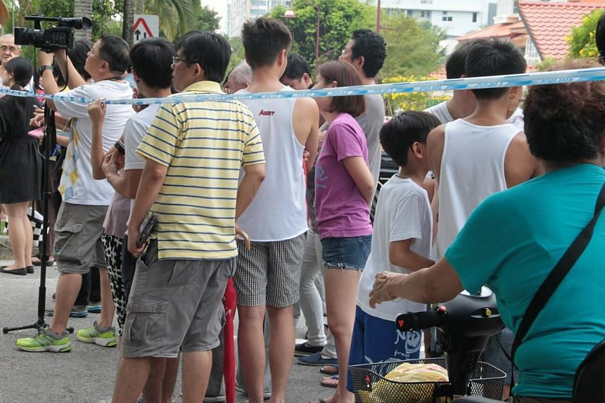 People gather along Hillside Drive on Saturday, July 13, 2013.  The Kovan murder suspect, 34-year-old Singapore policeman Iskandar Rahmat (not pictured), was taken by police to the crime scene at Hillside Drive at about 2.15pm on Saturday. -- PH