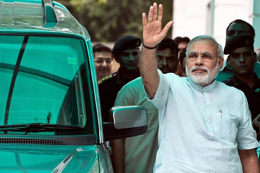 Head of the Bharatiya Janata Party (BJP) poll panel and Gujarat chief minister Narendra Modi waves on his arrival at party headquarters for the BJP's Parliamentary Board meeting in New Delhi on Monday, July 8, 2013. Mr Modi, seen as the key oppositio