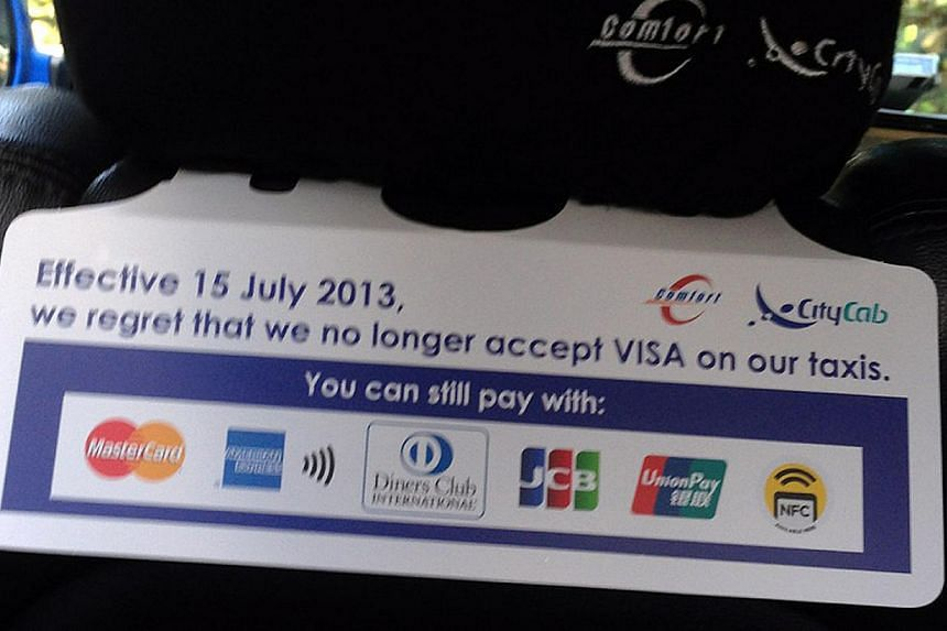 A sign in a Comfort taxi informing passengers that payment by Visa will no longer be accepted (below).
