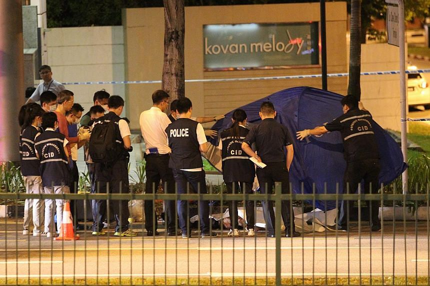 Police standing around the younger Mr Tan's body outside Kovan MRT station on Wednesday. He had been dragged there by a car.